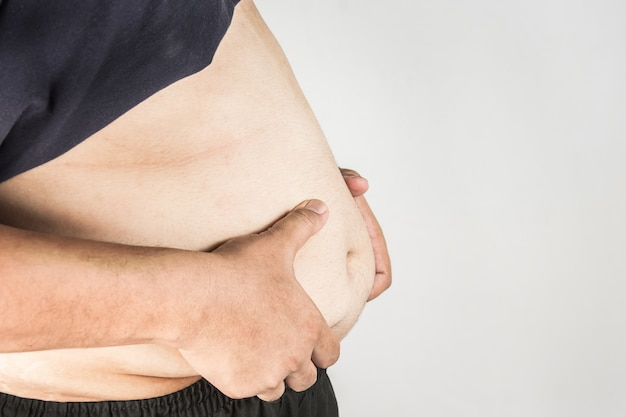 Overweight man body with hands touching belly fat