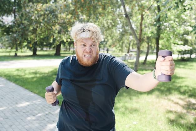 공원에서 훈련하는 동안 온 힘을 다해 아령으로 운동하는 과체중 남자
