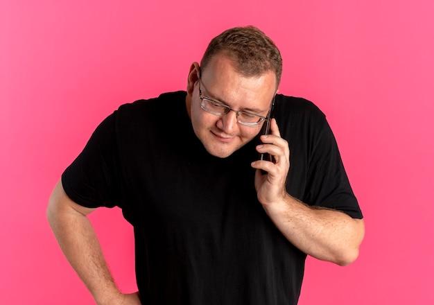 Uomo in sovrappeso con gli occhiali che indossa la maglietta nera sostenendo mentre parla al telefono cellulare in piedi sopra il muro rosa