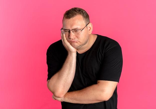 Uomo in sovrappeso con gli occhiali che indossa la maglietta nera infastidito appoggiando la testa sul braccio in attesa sul rosa