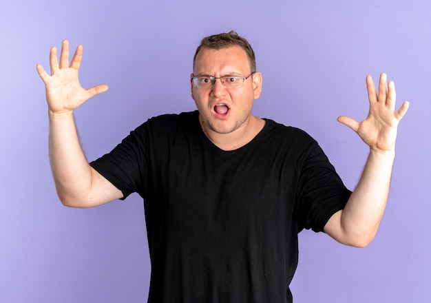 Overweight man in glasses wearing black t-shirt frustrated going wild shouting with angry face and raised arms over blue