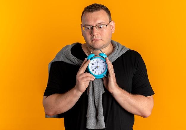 Uomo in sovrappeso con gli occhiali che indossa la maglietta nera che tiene l'orologio di alaem che sembra confuso non avendo risposta sull'arancia