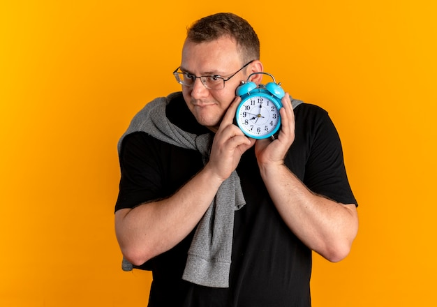 Overweight man in glasses wearing black t-shirt holding alaem clock near his ear standing over orange wall