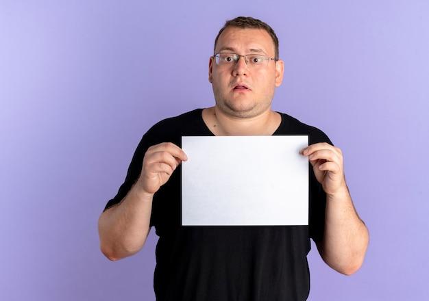 Uomo in sovrappeso con gli occhiali che indossa la maglietta nera che tiene un foglio di carta bianco confuso in piedi sopra la parete blu