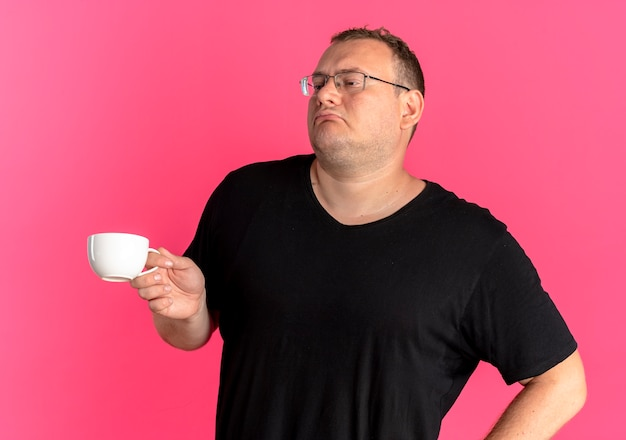 Uomo in sovrappeso con gli occhiali che indossa la maglietta nera che tiene la tazza di caffè che sembra soddisfatto di sé sul rosa