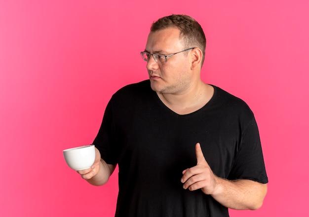 Uomo in sovrappeso con gli occhiali che indossa la maglietta nera che tiene tazza di caffè che mostra il dito indice sopra il rosa