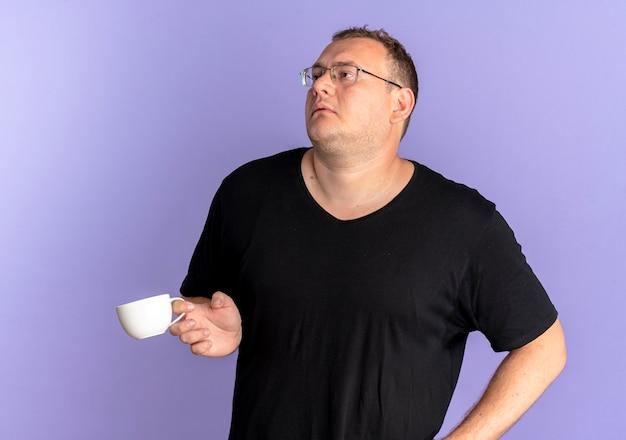 Uomo in sovrappeso con gli occhiali che indossa la maglietta nera che tiene la tazza di caffè stanco e annoiato sopra l'azzurro