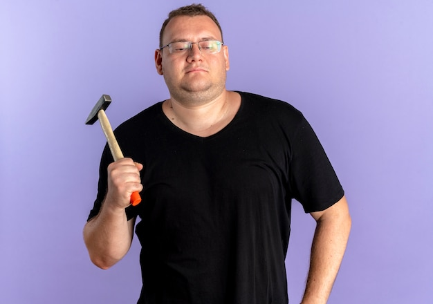 Overweight man in glasses wearing black t-shirt holding hammer looking confident over blue