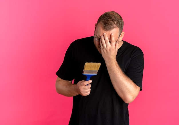 Overweight man in glasses wearing black t-shirt holding paint brush covering face with hand disappointed standing over pink wall
