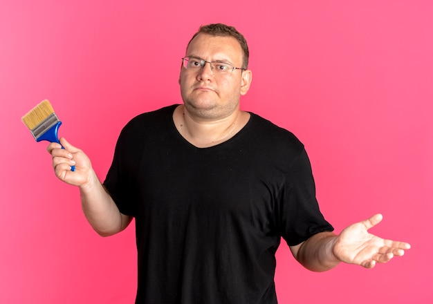 Uomo in sovrappeso con gli occhiali che indossa una maglietta nera che tiene il pennello diffondendo il braccio di lato guardando confuso sul rosa