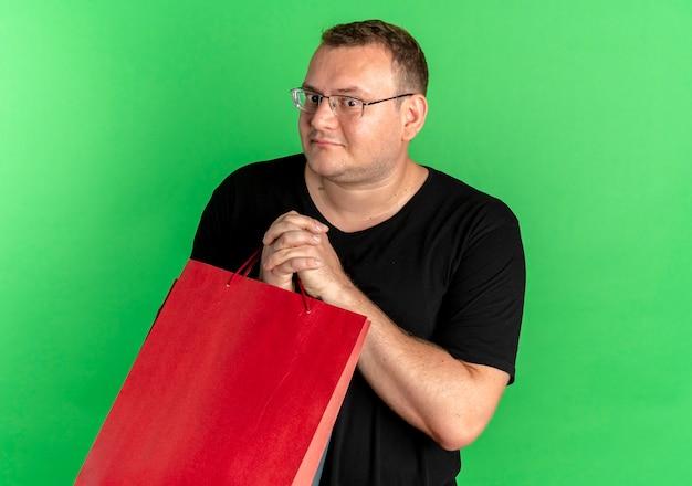 Uomo in sovrappeso con gli occhiali che indossa la maglietta nera che tiene i sacchetti di carta che sembrano confusi in piedi sopra la parete verde