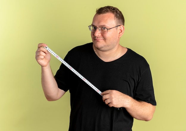 Overweight man in glasses wearing black t-shirt holding ruler  with smile on face standing over light wall
