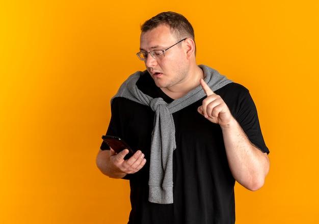 Uomo in sovrappeso con gli occhiali che indossa la maglietta nera che tiene lo smartphone che sembra confuso che mostra il dito indice sopra l'arancio