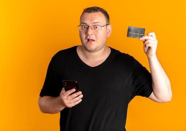 Uomo in sovrappeso con gli occhiali che indossa la maglietta nera che tiene lo smartphone che mostra il lookign della carta di credito sorpreso sull'arancia