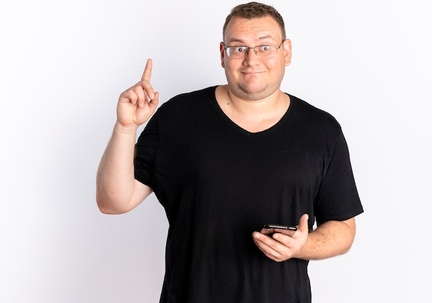 Overweight man in glasses wearing black t-shirt holding smartphone showing index finger having new idea standing over white wall