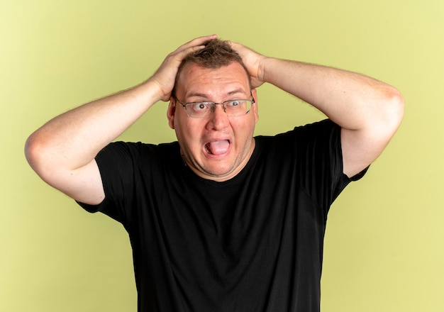 Overweight man in glasses wearing black t-shirt lookign aside pulling his hair in panic over light