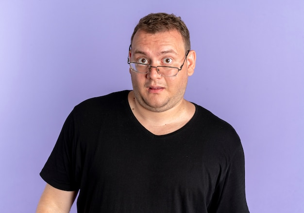 Overweight man in glasses wearing black t-shirt lookign at camera surprised and confused over blue