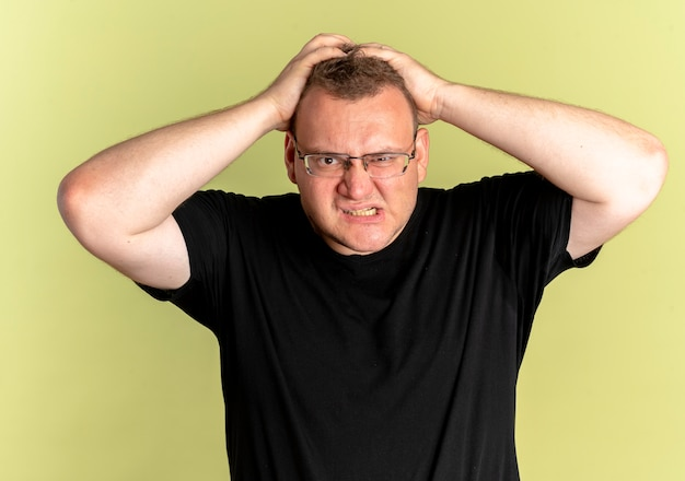 Overweight man in glasses wearing black t-shirt lookign at camera with angry face going wild pulling his hair over light
