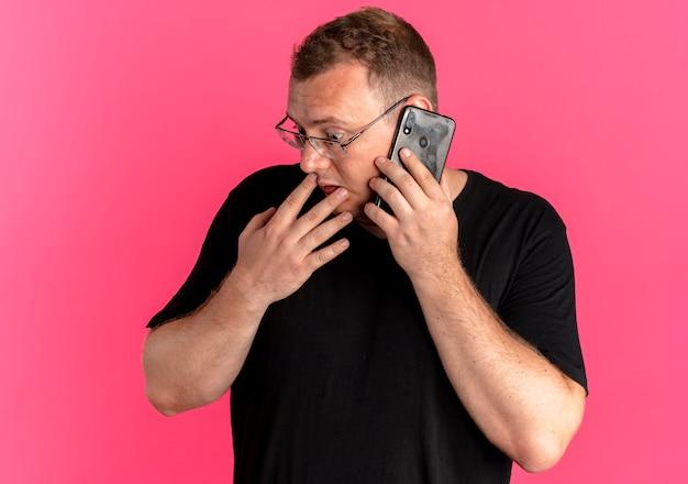 Uomo in sovrappeso con gli occhiali che indossa la maglietta nera che osserva da parte confuso mentre parla al telefono cellulare sopra il rosa