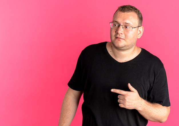 Uomo in sovrappeso con gli occhiali che indossa una maglietta nera che guarda da parte e punta il dito indice sul lato in piedi sopra il muro rosa