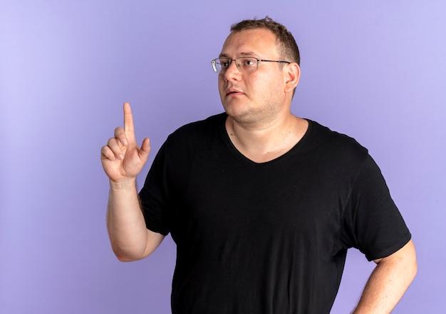 Uomo in sovrappeso con gli occhiali che indossa la maglietta nera che osserva da parte mostrando il dito indice che chiede di aspettare un minuto sopra il blu