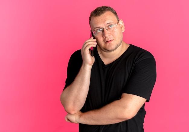 Uomo in sovrappeso con gli occhiali che indossa la maglietta nera che guarda da parte con espressione pensierosa mentre parla al telefono cellulare sopra il rosa