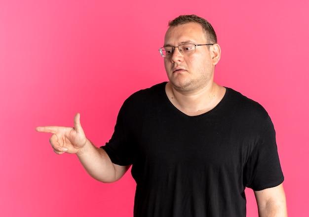 Uomo in sovrappeso con gli occhiali che indossa la maglietta nera che osserva da parte con la faccia seria che punta con il dito di lato sopra il rosa