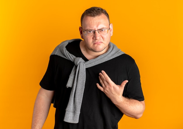 Uomo in sovrappeso con gli occhiali che indossa la maglietta nera che guarda l'obbiettivo scontento con il braccio fuori come chiedere o discutere in piedi sopra la parete arancione