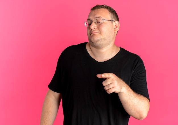 Uomo in sovrappeso con gli occhiali che indossa una maglietta nera che sembra fiducioso pointign con il dito indice a lato sopra il rosa
