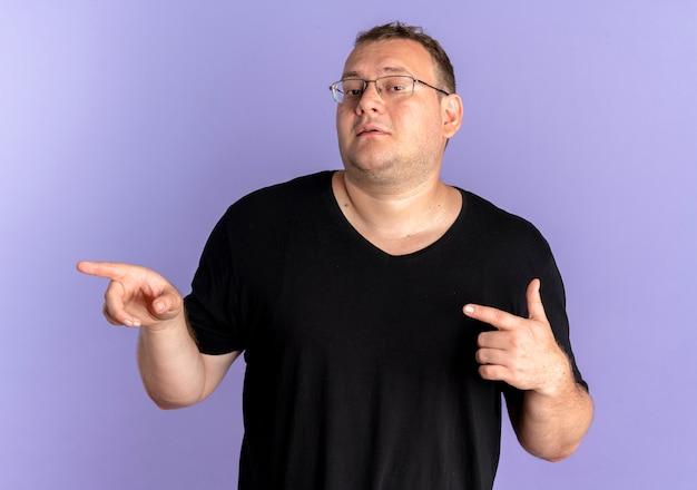 Uomo in sovrappeso con gli occhiali che indossa una maglietta nera che sembra fiducioso pointign con le dita indice a lato sopra il blu