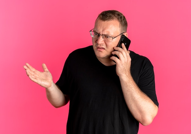 Overweight man in glasses wearing black t-shirt looking confused and displeased while talking on mobile phone over pink