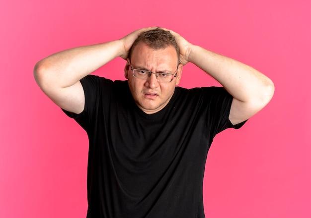 Uomo in sovrappeso con gli occhiali che indossa una maglietta nera che sembra confuso tenendo la testa con le mani sul rosa