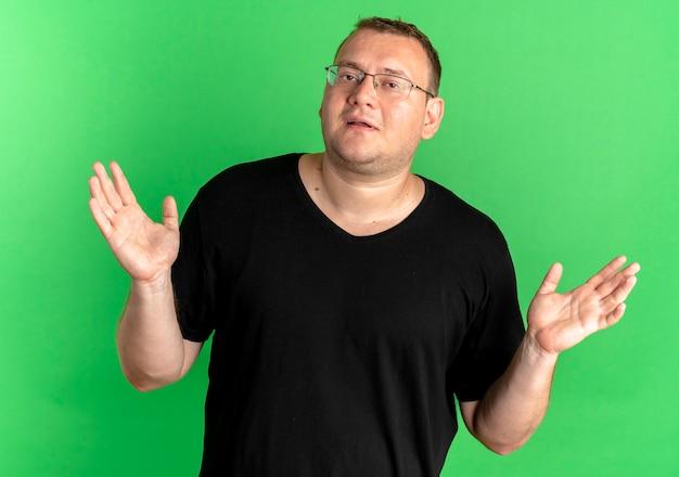 Uomo in sovrappeso con gli occhiali che indossa una maglietta nera che sembra confuso e incerto allargando le braccia ai lati senza risposta sul verde