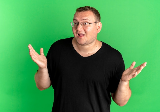 Overweight man in glasses wearing black t-shirt looking confused and uncertain spreading arms to the sides having no answer over green