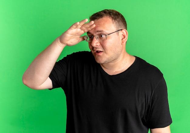 Uomo in sovrappeso con gli occhiali che indossa la maglietta nera che guarda lontano con la mano sulla fronte sorpreso in piedi sopra la parete verde