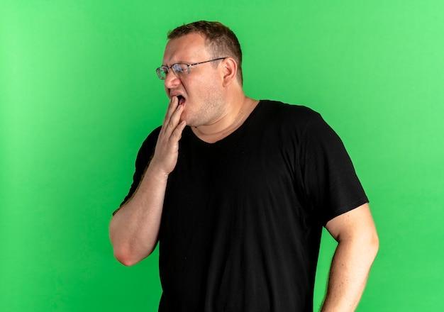 Uomo in sovrappeso con gli occhiali che indossa la maglietta nera che sembra stanco sbadigliare sul verde