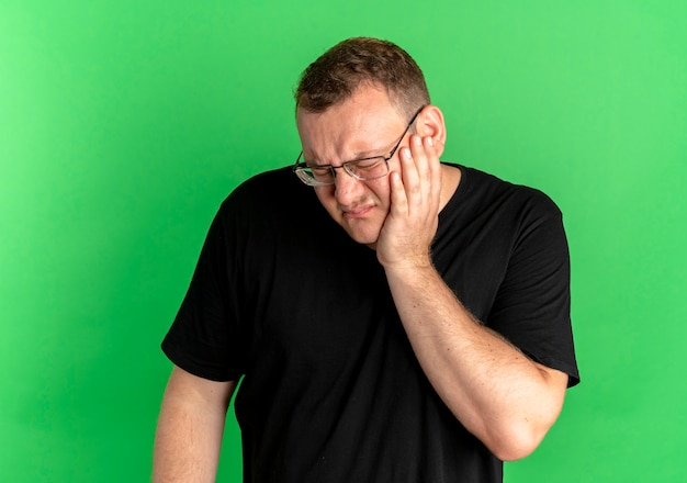 Uomo in sovrappeso con gli occhiali che indossa una maglietta nera che sembra malato toccando la guancia con mal di denti sul verde
