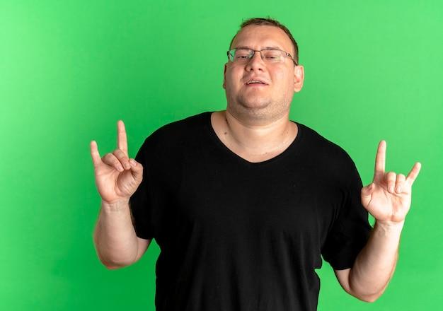 Uomo in sovrappeso con gli occhiali che indossa la maglietta nera che fa il simbolo della roccia che sembra fiducioso sul verde