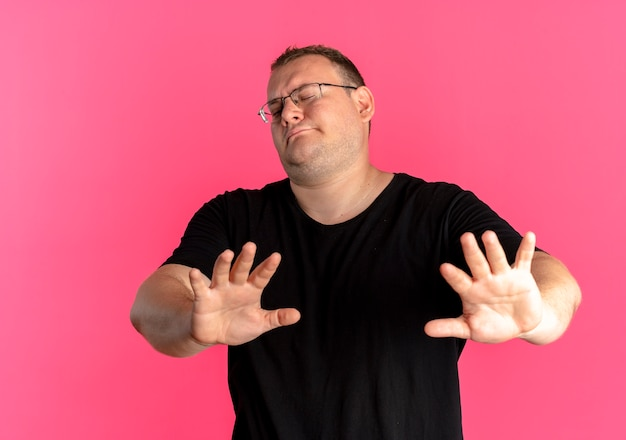 Overweight man in glasses wearing black t-shirt making stop sing holding hands out as telling do not come closer standing over pink wall
