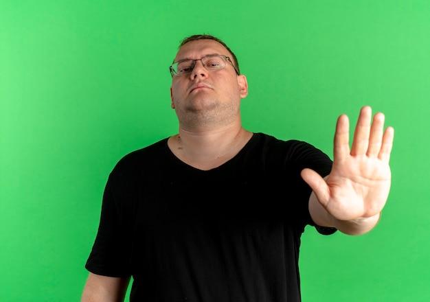 Uomo in sovrappeso con gli occhiali che indossa una maglietta nera che fa smettere di cantare con la mano aperta con la faccia seria in piedi sopra la parete verde