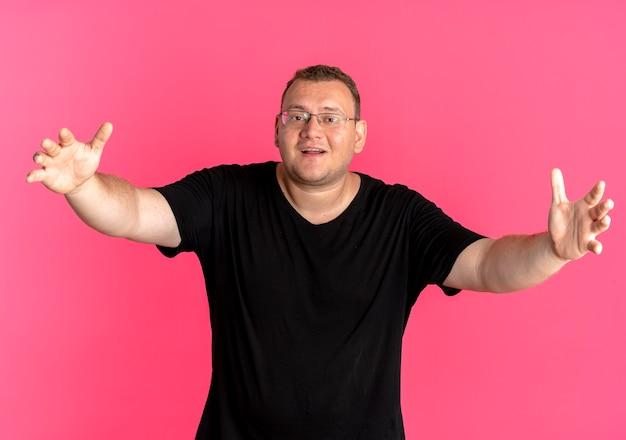 Uomo in sovrappeso con gli occhiali che indossa la maglietta nera che fa il gesto di benvenuto con le mani in piedi sul muro rosa