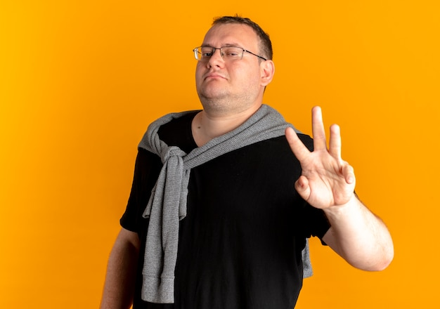 Overweight man in glasses wearing black t-shirt showing and pointing up with fingers number three over orange