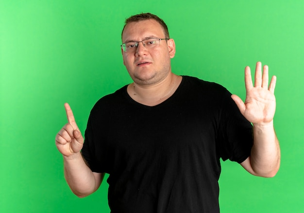 Overweight man in glasses wearing black t-shirt showing and pointiogn up with fingers number six over green
