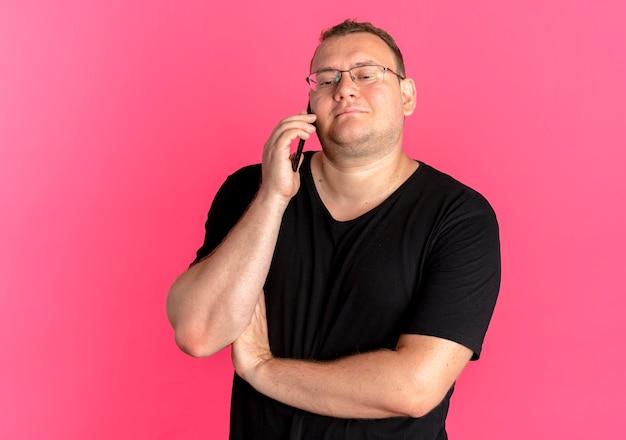 Uomo in sovrappeso con gli occhiali che indossa la maglietta nera sorridente mentre parla al telefono cellulare sopra il rosa