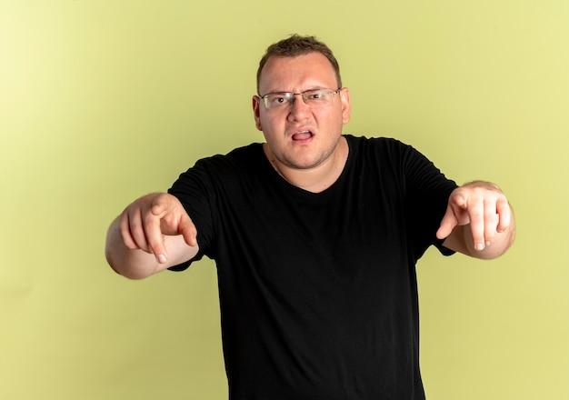 Uomo in sovrappeso con gli occhiali che indossa una maglietta nera con la faccia arrabbiata che punta con le dita in piedi sopra la parete chiara