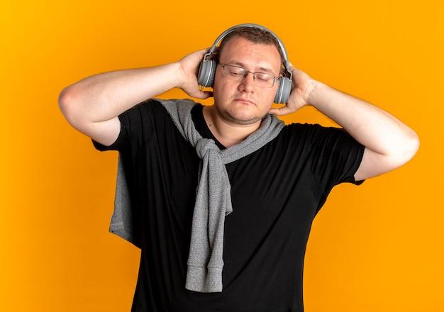 Uomo in sovrappeso con gli occhiali che indossa la maglietta nera con le cuffie per godersi la musica in piedi sopra la parete arancione