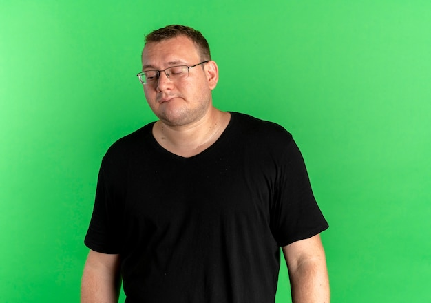 Overweight man in glasses wearing black t-shirt with sad expression on face standing over green wall