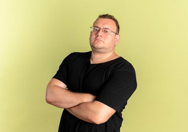 Uomo in sovrappeso con gli occhiali che indossa una maglietta nera con seriosu espressione sicura con le braccia incrociate sul petto in piedi sopra la parete chiara