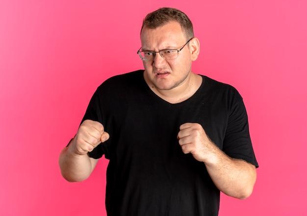 ピンクの上に怒った顔で見て拳を握り締める黒いtシャツを着て眼鏡をかけた太りすぎの男