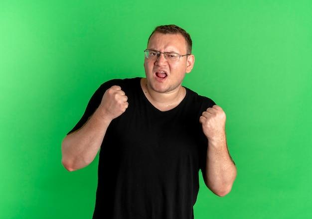 緑の壁の上に立って幸せで興奮した拳を握り締める黒いtシャツを着た眼鏡の太りすぎの男
